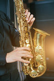 Musical instrument sax close-up. Musical instrument saxophone close-up. Hands on a musical instrument. Young guy playing jazz Royalty Free Stock Images