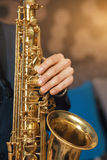 Musical instrument sax close-up. Musical instrument saxophone close-up. Hands on a musical instrument. Young guy playing jazz Stock Photography