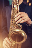 Musical instrument sax close-up. Musical instrument saxophone close-up. Hands on a musical instrument. Young guy playing jazz Royalty Free Stock Image