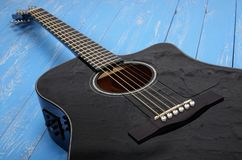 Musical instrument - Silhouette black cutaway electric acoustic. Musical instrument - Black cutaway electric acoustic guitar on a blue wood background royalty free stock photo
