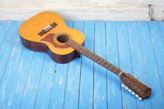 Musical instrument - Twelve-string acoustic guitar brick backgro. Musical instrument - Vintage twelve-string acoustic guitar on a brick background and blue royalty free stock photo