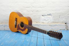 Musical instrument - Twelve-string acoustic guitar white brick b. Musical instrument - Vintage twelve-string acoustic guitar on a brick background and blue royalty free stock photos