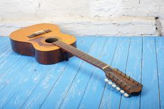 Musical instrument - Twelve-string acoustic guitar brick backgro. Musical instrument - Vintage twelve-string acoustic guitar on a brick background and blue stock photos