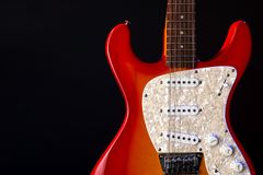Musical instrument wooden six-string guitar red isolated on blackbackground stock photo