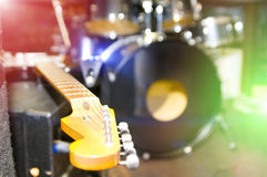 Musical instruments. On a stage, an electroguitar, drums, bright multi-coloured light Royalty Free Stock Photography