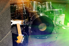 Musical instruments. On a stage, an electroguitar, drums, bright multi-coloured light Stock Photography