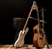 Musical instruments, acoustic guitar and bass guitar and percussion instruments drums. On a black background, the music concept Stock Photos