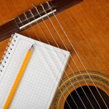 Musical instruments - the Acoustic guitar and a notebook. Royalty Free Stock Photo