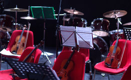 Musical instruments awaiting musicians. Violins resting on chairs at a concert Stock Photography