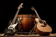Musical instruments, bass drum barrel acoustic guitar and bass guitar on a black background. The music concept Stock Photography