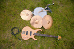 Musical instruments, guitar, drum, plates on grass Stock Image
