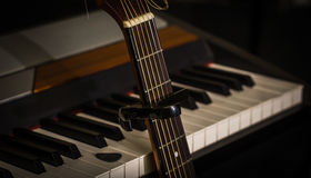 Musical instruments piano keys and acoustic guitar capadaster Stock Photography