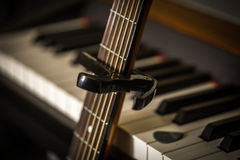 Musical instruments piano keys and acoustic guitar capadaster Royalty Free Stock Photo