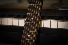 Musical instruments piano keys and acoustic guitar Stock Images