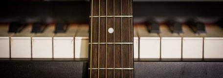 Musical instruments piano keys and acoustic guitar Stock Image