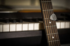 Musical instruments piano keys and acoustic guitar with plectrum Royalty Free Stock Images