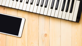 Musical keyboard with tablet on wood Royalty Free Stock Photography