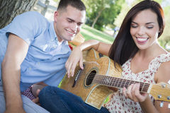 Musical Mixed Race Couple at the Park Playing Guitar and Singing Royalty Free Stock Images
