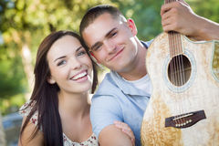 Musical Mixed Race Couple Portrait with Guitar in Park Royalty Free Stock Images