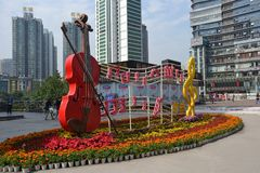 Musical Monument in Chongquin, China. This is a monument with violin and musical score in a plaza in Chongquin, China surrounded by office and apartment Stock Images
