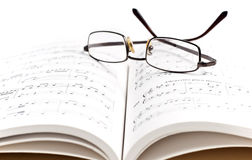 Musical note. Book with musical notes with glasses on it Stock Photos