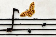Musical note. Butterfly and musical note on concrete wall Stock Photo