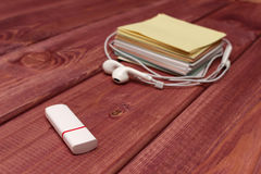 Musical note. Multicolored stickers and white headphones  are on a wooden table. View from above Stock Photos