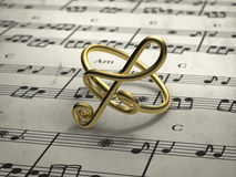 Musical note ring with score in background. Perspective view of musical note ring with score in background Stock Images