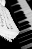 Musical notes. On composer over piano keys, black and white stock image