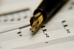 Musical notes. A fountain pen and a dull knife on a musical notes royalty free stock image