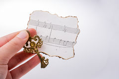 Musical notes on burnt paper in hand Royalty Free Stock Images