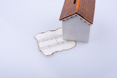 Musical notes on a burnt paper under a model house Stock Photos