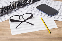 Musical notes and clarinet. On wooden table Royalty Free Stock Photos