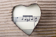 Musical notes and heart shaped burnt out of a cardboard Royalty Free Stock Photography