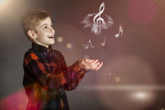 Musical Notes Over the Hands of a Happy Boy Stock Images