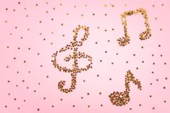 Musical notes of starry golden confetti lying on a pink pastel background. Musical notes of starry golden confetti lying on a pink pastel background stock photos
