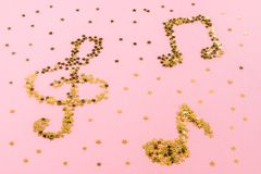 Musical notes of starry golden confetti lying on a pink pastel background. Musical notes of starry golden confetti lying on a pink pastel background royalty free stock photography