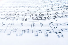 Musical notes on wavy white sheet of paper. Selective focus. stock images