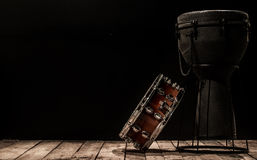 Musical percussion instruments on black background drum Bongo and snare. Stands on the wooden floor ,the concept of musical instruments Stock Photos