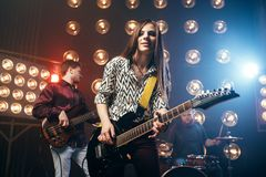Musical performers on the stage in night club. Vintage style. Guitarists and drummer, rock band concert, music show Royalty Free Stock Photography