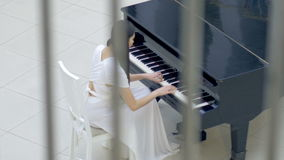 Musical pianist playing classical grand piano in a center of concert hall. Steadycam shot. Musical pianist playing classical grand piano in a center of concert stock video footage