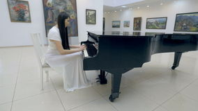 Musical pianist playing classical grand piano in a center of concert hall. Steadycam shot. stock video