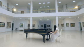 Musical pianist playing classical grand piano in a center of concert hall. Steadycam shot. stock video footage