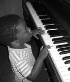Musical prodigy. Small African American child playing the piano. Black and White photo Royalty Free Stock Images