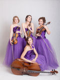 Musical quartet in evening dresses. With strings instruments Stock Photo