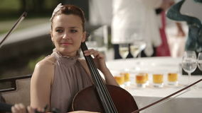 Musical quartet. Girl playing cello in a quartet of violinists. Medium shot. Musical quartet. Three violinists and cellist playing music stock footage