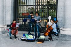 Musical quartet playing at the entrance of Opera Palace in Madri. Madrid, Spain - October 15, 2017: Musical quartet playing in the street at the entrance of Stock Photos