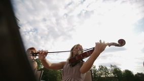 Musical quartet. Violinist plays against the sky. Medium shot. Musical quartet. Three violinists and cellist playing music. SESSION KEYWORD: uzhursky003 stock video