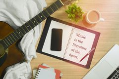 Acoustic Guitar, Notebook and Multiple Items with Musical Quote. Musical quote. Music is the literature of the art Stock Photo
