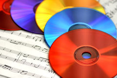 Musical Rainbow. A colorful array of CDs on sheet music is an eye-catching way to illustrate the concept of copying music onto CDs, listening to music, playing stock image